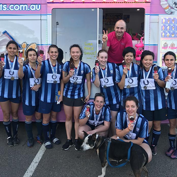 Soccer team eating ice cream form ice cream truck